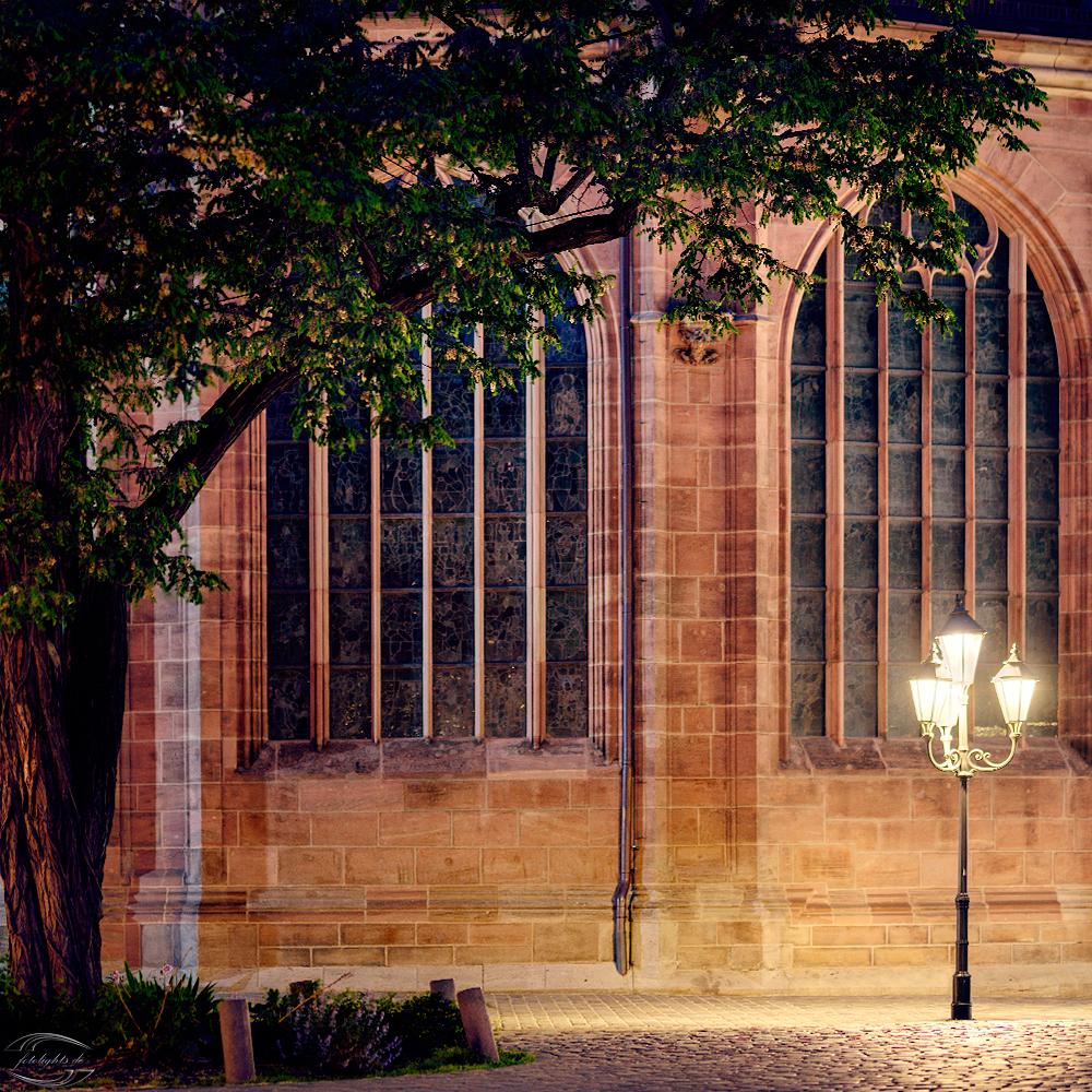 Bild einer Laterne mit einem Baum am Rand und der Lorenzkirche im Hintergrund