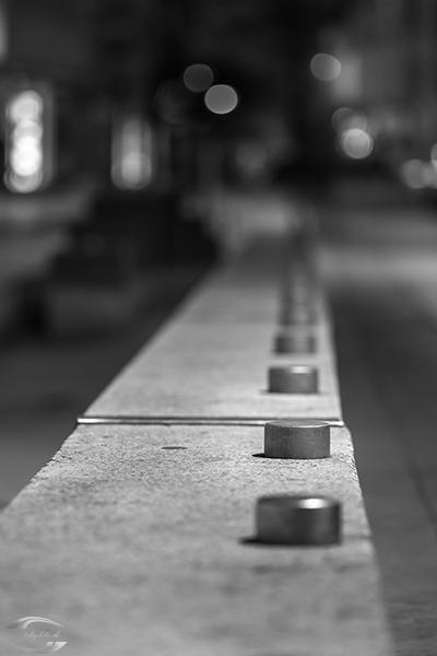 Metallzylinder auf einer Mauer in der Nacht in schwarz-weiß