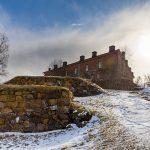 Bild zweir Gebäude an einem verschneiten Hügel