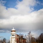 Leuchtturm mit leicht bewölktem blauen Himmel im Hintergrund