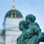 Bild zweier weiblichen Statuen mit einem weißen Turm unscharf im Hintergrund