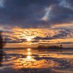 Panorama eines gefronenen Sees mit einem bewölkgem Himmel und der untegehenden Sonne am Horizont