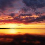 Wolken über einem See nach Sonnenuntergang