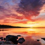 Panorama eines Sees nach Sonnenuntergang mit Wolken am Himmel
