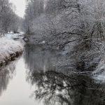 Blick einen Fluß entlang mit Reif überzogenen Bäumen am Ufer