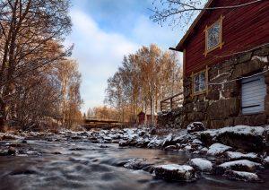 Bild eines winterlichen Flusses mit Blick flussaufwärts, rechts ein altes Haus