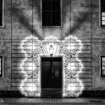 Blick auf den Eingang eines beleuchteten Gebäudes in schwarz-weiß
