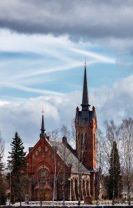 Kirche von Eura von rechts beschienen vor teilweise bewölktem Himmel