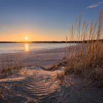Blick einen Strand entlang bei Sonnenuntergang