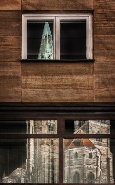 Türme der Sebalduskirche spiegeln sich in Fenstern
