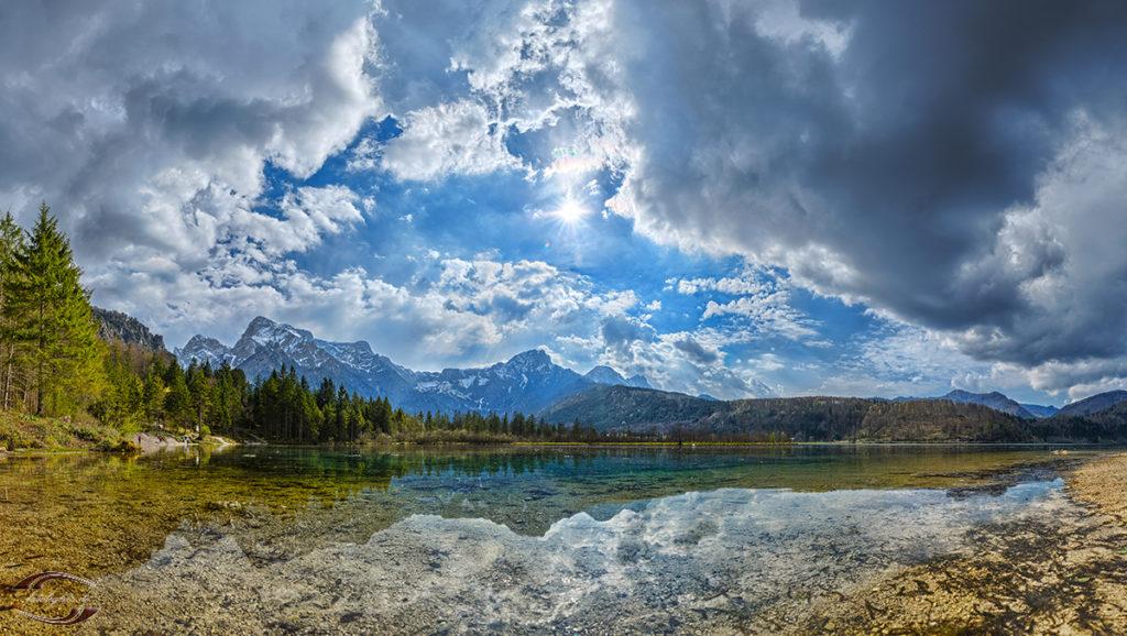 Panorama eines Alpensees mit den Bergen im Hintergrund