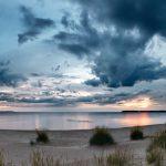 Panorma eines Strandes zur Blauen Stunde mit Wolken am Himmel