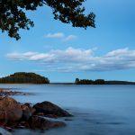 Blick über einen See Richtung zwei Inseln mit Steinen im Vordergrund links