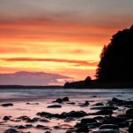 Abendrot an einem See mit Steinen im Vordergrund