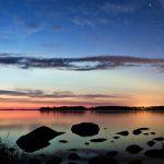 Panorama eines Sees am Abend mit dem Rest Abendrot am Horizont und Steinen im Vordergrund