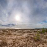 Panorma eines Strandes mit der untergehenden Sonne über dem Horizont