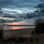 Blick vorbei an Dünengras über das Wasser an einem Strand zur Blauen Stunde mit Wolken am Himmel