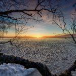 Blick über einen vereisten See vom Ufer aus mit der Sonne am Horizont