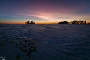 Blick über einen verschneiten See in der Dämmerung mit Inseln im Hintergrund