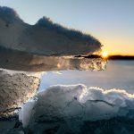 Blick durch Eisformen hindurch mit der Sonne am Horizont