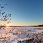 Blick über eine verschneite Fläche mit der Sonne am Horizont