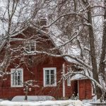 Blick auf ein rotes Haus mit verscheiten kahlen Bäumen davor