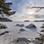 Blick über einen verschneiten See vom Ufer aus