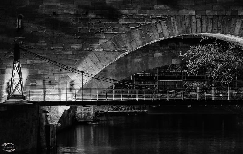Teil des Kettenstegs mit verschwommener Person in schwarz-weiß bei Nacht
