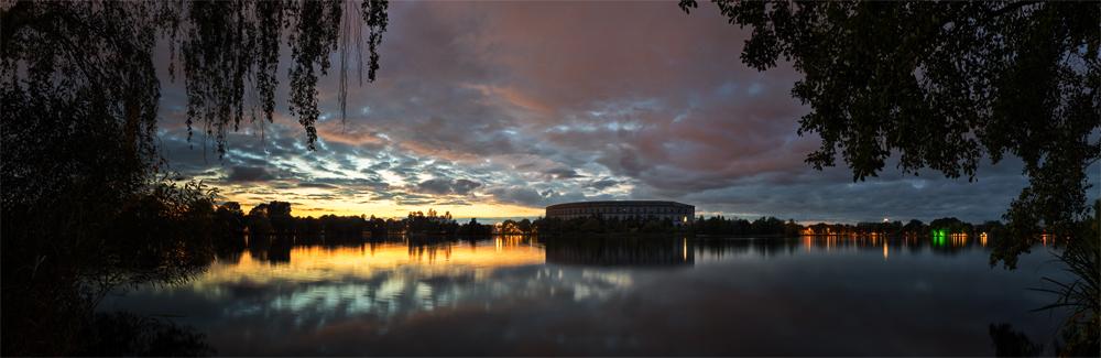 Panorama eines Sees mit dem Nürnberger Koloseum am Abend
