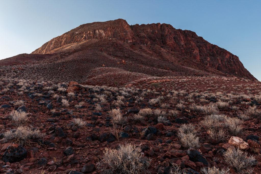 Bild am Fuss eines Berges mit Gras im Vordergrund