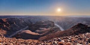 Blick über einen Cayon mit der Sonne nahe dem Horizont