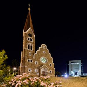 Kirche und ein modernes Gebäude im Hintergrund bei Nacht