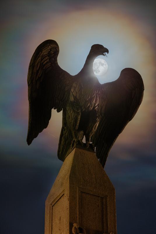 Vollmond hinter der Statue eines Vogels