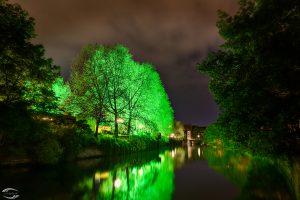 Blick auf die Pegnitz in der Nacht mit einem grün beleuchteten Baum am linken Ufer