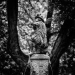 Bild einer Statue eines Bogenschützen vor Bäumen