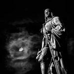 Statue mit Mond im Hintergrund in schwarz-weiß