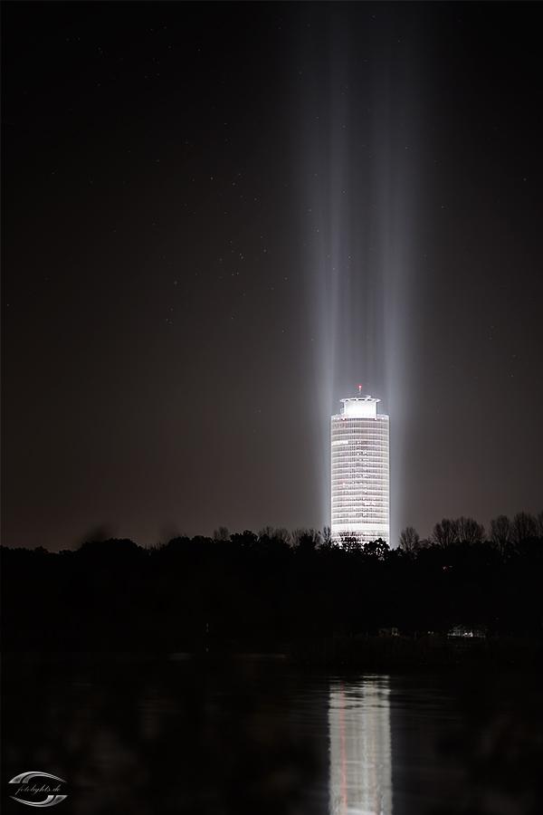 Ein sich im Wasser spiegelnder beleuchteter Turm bei Nacht