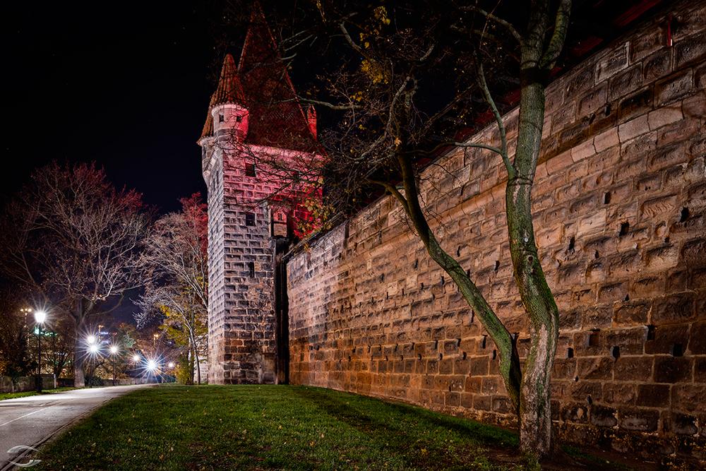 Blick entlang der Burgmauer auf einen rot angestrahlten Turm