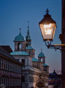 Bild eines historischen Gebäudes im Hintergrund mit einer Lampe im Vordergrund