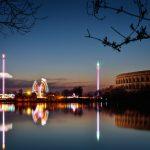 Blick über einen See auf Fahrgeeschäfte und das Nürnberger Kolloseum bei Nacht