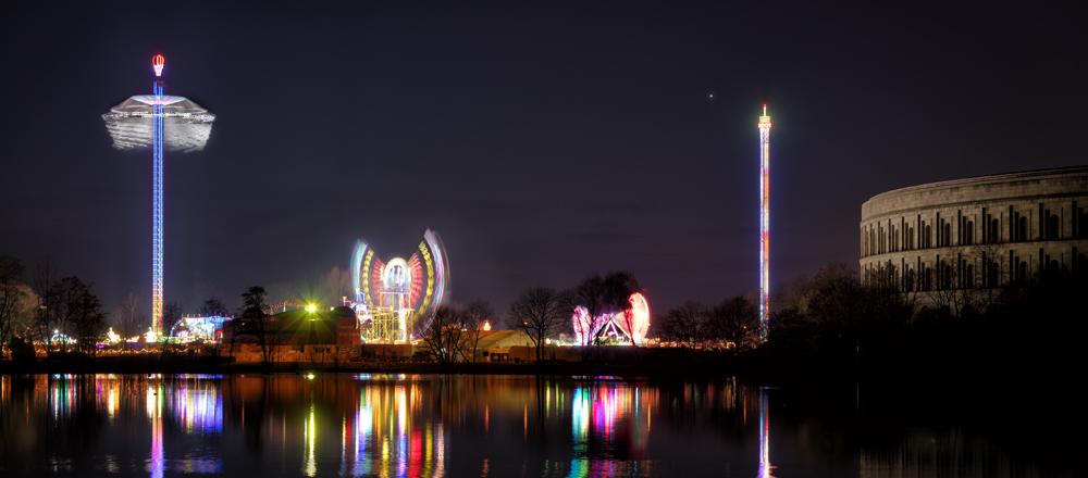 Blick über einen See auf Fahrgeeschäfte bei Nacht