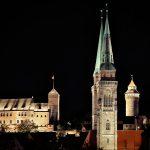 Türme der Sebalduskirche mit der Kaiserburg im Hintergrund bei Nacht