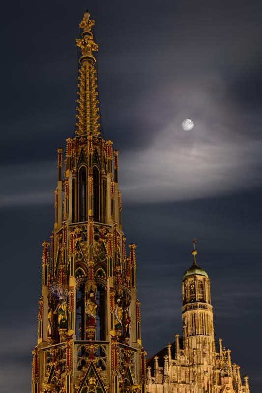 Schöner Brunnen und Frauenkirche mit Mond darüber bei Nacht