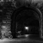 Schwarz-Weiß-Bild eines Steintores mit einem Fahrrad am linken Rand