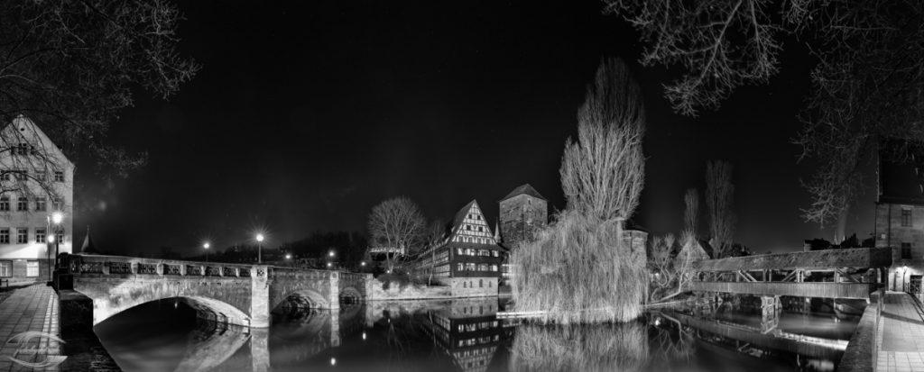 Schwarz-Weiß-Bild vom Weinstadl und zweier Bäume an einem Fluss bei Nacht im Winter