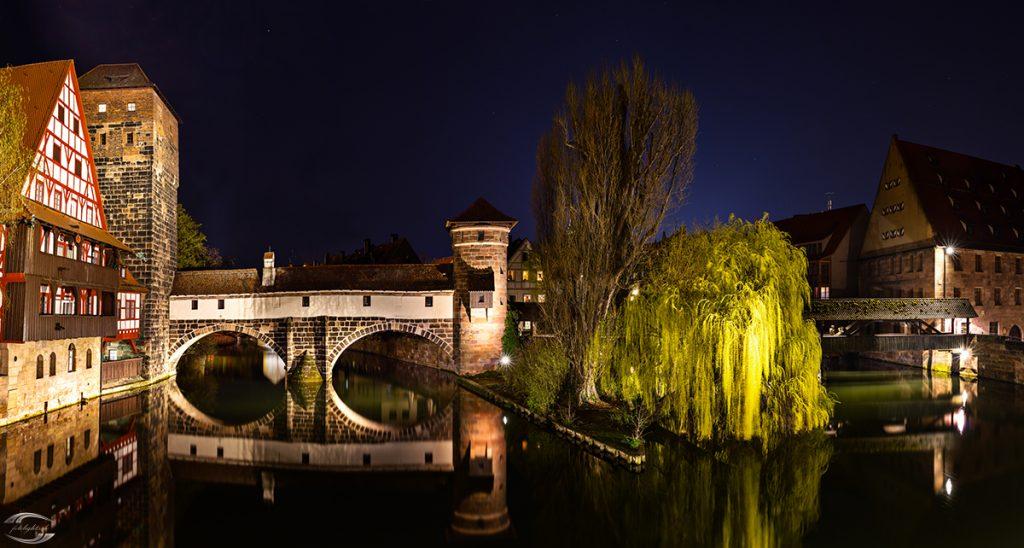 Bild vom Weinstadl und zweier Bäume an einem Fluss bei Nacht