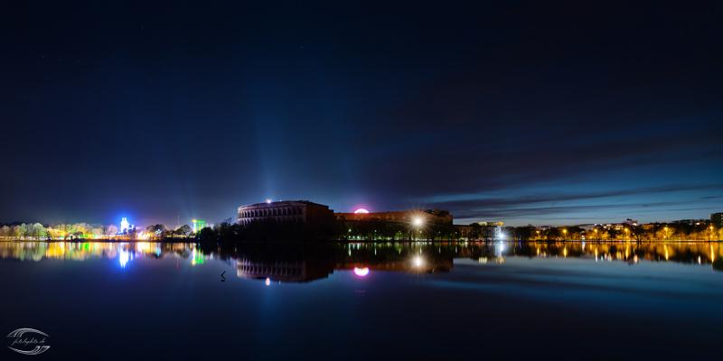 Blick über einen See mit dem Nürnberger Kolloseum und Fahrgeschäften im Hintergrund zur Blauen Stunde