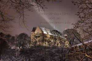 Bild der Kaiserburg durch verschneites Geäst mit dem Schriftzug Frohe Weihnachten und ein gesundes neues Jahr im Himmel