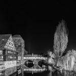 Schwarz-Weiß-Bild vom Weinstadl und zweier Bäume an einem Fluss bei Nacht